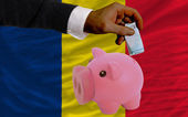 Funding euro into piggy rich bank national flag of of chad — Stock Photo