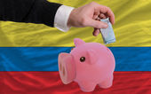 Funding euro into piggy rich bank national flag of columbia — Stock Photo