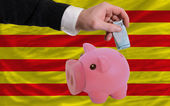 Funding euro into piggy rich bank national flag of of catalonia — Stock Photo