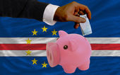 Funding euro into piggy rich bank national flag of of capeverde — Stock Photo
