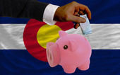 Funding euro into piggy rich bank flag of american state of colo — Stock Photo