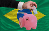 Funding euro into piggy rich bank national flag of brazil — Stock Photo