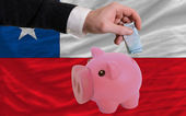Funding euro into piggy rich bank national flag of chile — Stock Photo