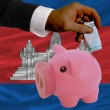Funding euro into piggy rich bank national flag of cambodia — Stock Photo