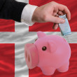 Funding euro into piggy rich bank national flag of denmark - Foto Stock