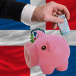 Funding euro into piggy rich bank national flag of dominican - Stock Photo