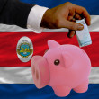 Funding euro into piggy rich bank national flag of costarica - Foto de Stock  
