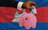Funding euro into piggy rich bank national flag of cambodia — Stock fotografie