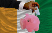 Funding euro into piggy rich bank national flag of cote ivore — Stock Photo