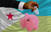Funding euro into piggy rich bank national flag of of djibuti — Stock Photo