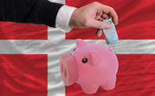 Funding euro into piggy rich bank national flag of denmark — Stock Photo