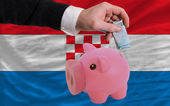Funding euro into piggy rich bank national flag of croatia — Stock Photo