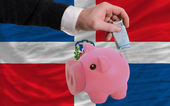 Funding euro into piggy rich bank national flag of dominican — Stock Photo