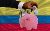 Funding euro into piggy rich bank national flag of ecuador — Стоковое фото