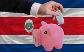 Funding euro into piggy rich bank national flag of costarica — Stock Photo