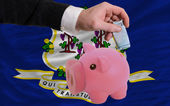 Funding euro into piggy rich bank flag of american state of conn — Stock Photo