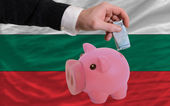Funding euro into piggy rich bank national flag of bulgaria — Stock Photo