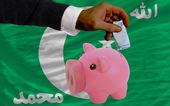 Funding euro into piggy rich bank national flag of of comoros — Stock Photo