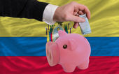 Funding euro into piggy rich bank national flag of ecuador — Stock Photo