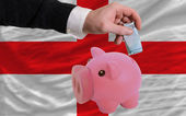 Funding euro into piggy rich bank national flag of england — Stock Photo