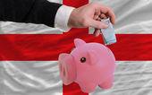 Funding euro into piggy rich bank national flag of england — Stock Photo