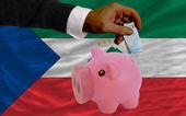 Funding euro into piggy rich bank national flag of of equatoria — Стоковое фото