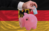 Funding euro into piggy rich bank national flag of germany — Stock Photo