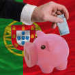 Funding euro into piggy rich bank national flag of portugal - Stok fotoraf
