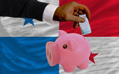 Funding euro into piggy rich bank national flag of panama — Stockfoto