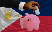 Funding euro into piggy rich bank national flag of philippines — Стоковое фото