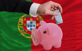 Funding euro into piggy rich bank national flag of portugal — Стоковое фото