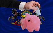 Funding euro into piggy rich bank flag of american state of penn — Stock Photo