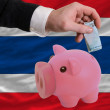 Funding euro into piggy rich bank national flag of thailand - Foto de Stock  