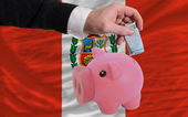 Funding euro into piggy rich bank national flag of peru — Stock fotografie