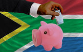 Funding euro into piggy rich bank national flag of south africa — Stock Photo