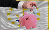 Funding euro into piggy rich bank flag of american state of rhod — Стоковое фото