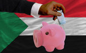 Funding euro into piggy rich bank national flag of sudan — Stock Photo