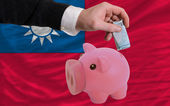 Funding euro into piggy rich bank national flag of taiwan — Stock Photo