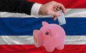 Funding euro into piggy rich bank national flag of thailand — Stock Photo