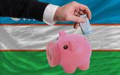 Funding euro into piggy rich bank national flag of uzbekistan — Stock Photo