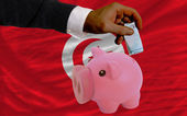 Funding euro into piggy rich bank national flag of tunisia — Stock Photo