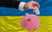 Funding euro into piggy rich bank national flag of ukraine — Stock Photo