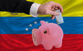Funding euro into piggy rich bank national flag of venezuela — Stock Photo