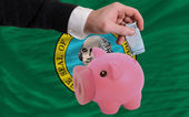 Funding euro into piggy rich bank flag of american state of wash — Stock Photo