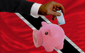 Funding euro into piggy rich bank national flag of trinidad toba — Stock Photo