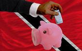 Funding euro into piggy rich bank national flag of trinidad toba — Stock Photo