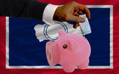 Funding euro into piggy rich bank flag of american state of wyom — Stock Photo