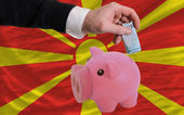 Funding euro into piggy rich bank national flag of macedonia — Stock Photo