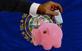 Funding euro into piggy rich bank flag of american state of new — Stock Photo