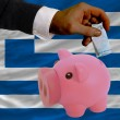 Funding euro into piggy rich bank national flag of greece - Stock Photo
